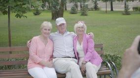 帽子的未被认出的人做照片他的朋友坐一条长凳在公园 两名可爱的喜悦妇女和人 影视素材