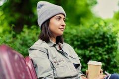帽子的深色的女性在夏天公园喝咖啡 库存图片