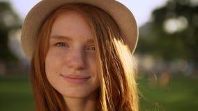 帽子的特写镜头柔和的可爱的夫人有精密红色长的头发的看照相机感人的头发微笑在明亮期间的 股票录像