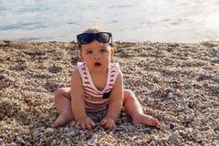 帽子的男婴在海滩小卵石 图库摄影