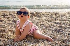 帽子的男婴在海滩小卵石 免版税库存照片