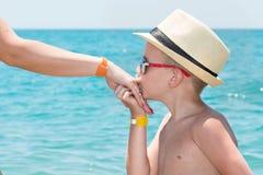帽子的男孩,亲吻在沿海的母亲的手 免版税库存图片