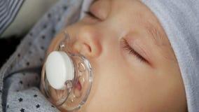 帽子的男婴与安慰者的四个月睡觉 股票录像