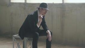帽子的画象英俊的确信的人投掷并且捉住坐在一个被放弃的大厦的硬币 ?  股票录像