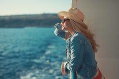 帽子的白肤金发的妇女在看的游轮  免版税图库摄影
