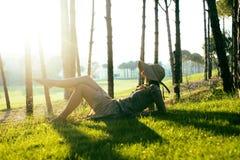 帽子的秀丽女孩在放置在草的日落的高尔夫球领域 生活 库存照片
