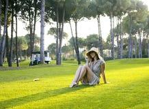 帽子的秀丽女孩在放置在草的日落的高尔夫球领域 生活 免版税库存照片