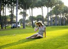 帽子的秀丽女孩在放置在草的日落的高尔夫球领域 生活 图库摄影