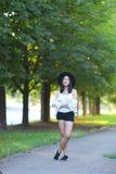 帽子的美丽的亚裔妇女调查照相机画象 免版税库存图片