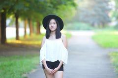 帽子的美丽的亚裔妇女调查照相机画象 库存照片