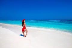帽子的美丽的妇女享受在异乎寻常的海滩的暑假 免版税库存图片