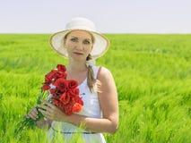 帽子的美丽的妇女在一个绿色领域 图库摄影