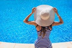 帽子的美丽的妇女坐游泳池边缘  免版税库存图片