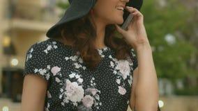 帽子的美丽的妇女谈话在手机特写镜头,小配件通信 股票视频