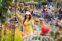 帽子的美丽的妇女走在annualy节日的果子庭院的 免版税库存图片