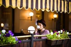 帽子的美丽的少妇坐在咖啡馆的一个大阳台,喝茶并且看照相机 库存照片
