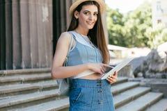帽子的美丽的年轻女人使用数字片剂和微笑对照相机,当站立时 免版税库存图片