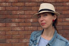 帽子的美丽的年轻女人确信地看照相机并且微笑着,当站立对白色砖墙时 库存图片
