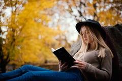 帽子的美丽的年轻金发碧眼的女人坐下落的秋叶在公园,读书 免版税图库摄影