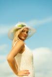帽子的美丽的白肤金发的女孩在天空背景 库存图片