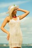 帽子的美丽的白肤金发的女孩在天空背景 免版税库存图片