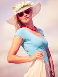 帽子的美丽的白肤金发的女孩在海滩 库存图片