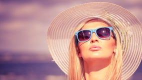 帽子的美丽的白肤金发的女孩在海滩 免版税库存照片