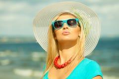 帽子的美丽的白肤金发的女孩在海滩 免版税库存图片