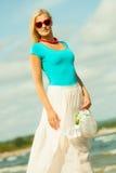 帽子的美丽的白肤金发的女孩在海滩 库存照片