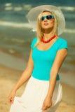 帽子的美丽的白肤金发的女孩在海滩 免版税图库摄影