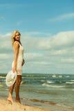 帽子的美丽的白肤金发的女孩在海滩 图库摄影