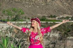 帽子的美丽的白肤金发的女孩站立与被伸出的胳膊 在背景中山和山沟 愉快 免版税库存图片