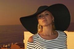 帽子的美丽的白肤金发的妇女。Sunset.sea.夏天 免版税库存图片