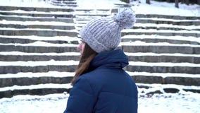 帽子的美女和冬季衣服对照相机微笑,当神色并且享受好天气时 情感摆在正随风飘飞的雪木头的时装模特儿 年轻 股票录像