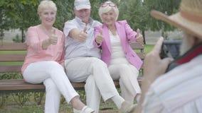 帽子的老人做照片他的朋友坐一条长凳在公园 两可爱喜悦妇女和人休息 股票录像