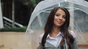 帽子的迷人的年轻女商人走与沿一个老镇的街道的伞的 美女是愉快的,她 影视素材