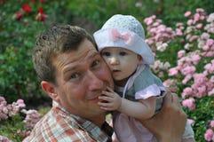 帽子的逗人喜爱的女婴拥抱她微笑的父亲 免版税库存图片
