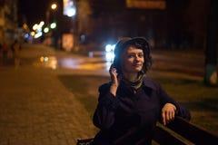 帽子的逗人喜爱的女孩坐长凳在晚上 免版税库存图片