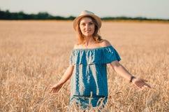 帽子的逗人喜爱的愉快的妇女在夏天麦田 图库摄影