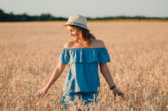 帽子的逗人喜爱的愉快的妇女在夏天麦田 免版税库存图片