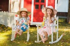 帽子的逗人喜爱的矮小的白肤金发的女孩坐与软的玩具的领域在夏天 库存图片