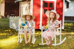 帽子的逗人喜爱的矮小的白肤金发的女孩坐与软的玩具的领域在夏天 免版税库存图片