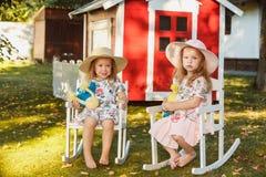 帽子的逗人喜爱的矮小的白肤金发的女孩坐与软的玩具的领域在夏天 库存照片