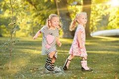 帽子的逗人喜爱的矮小的白肤金发的女孩坐与软的玩具的领域在夏天 图库摄影