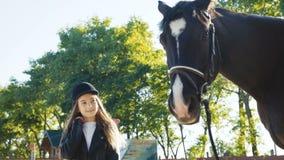 帽子的逗人喜爱,女孩来,注视着并且摆在黑母马` s头 股票视频