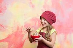 帽子的,围裙小愉快的女孩厨师用曲奇饼滚保龄球 免版税库存图片