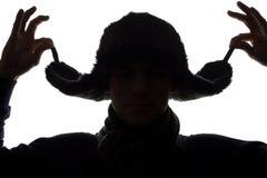 帽子的年轻人和手套朝前看-水平的剪影 免版税库存照片