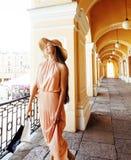 帽子的年轻俏丽的微笑的妇女有在购物的袋子的在商店 免版税库存图片