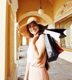 帽子的年轻俏丽的微笑的妇女有在购物的袋子的在商店 免版税库存照片