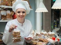 帽子的年轻厨师在糖果店显示用酥皮点心 免版税库存照片